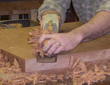[IMAGE: JP is hand planing a large Mahogany board]